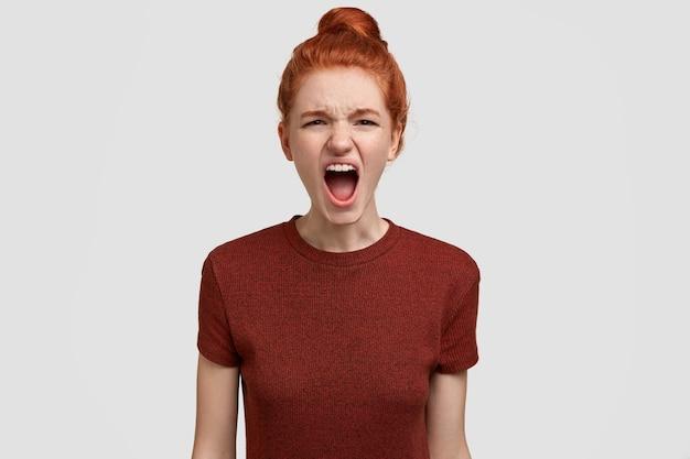 Foto van geïrriteerde roodharige vrouwelijke tiener schreeuwt luid, voelt zich geïrriteerd Gratis Foto