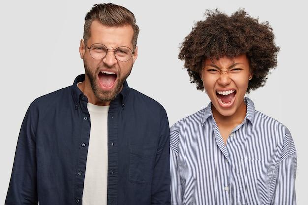 Foto van gekke boze jonge man en vrouw van verschillende rassen roepen geïrriteerd uit Gratis Foto