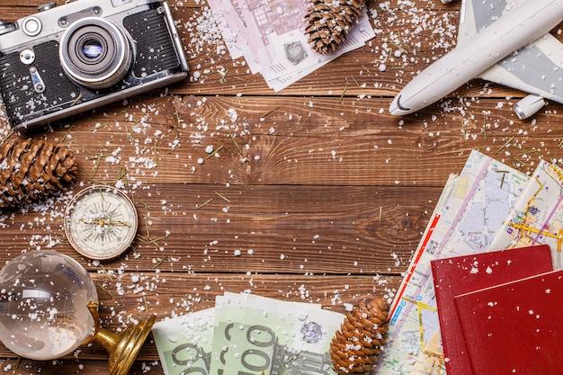 Foto van geld, sneeuw, paspoorten, vliegtuig, globe op houten achtergrond Premium Foto