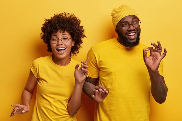 Foto van gelukkige afrikaanse paar dansen samen tegen gele achtergrond, lichaam actief bewegen Gratis Foto