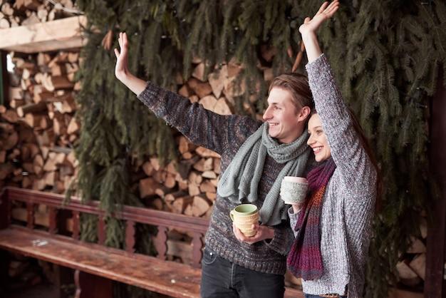 Foto van gelukkige man en mooie vrouw met koppen openlucht in de winter. wintervakantie en vakantie. kerst paar gelukkige man en vrouw drinken warme koffie. hallo buren Premium Foto