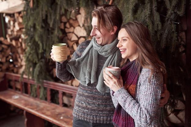 Foto van gelukkige man en mooie vrouw met koppen openlucht in de winter. wintervakantie en vakantie. kerst paar gelukkige man en vrouw drinken warme wijn. verliefd stel Premium Foto
