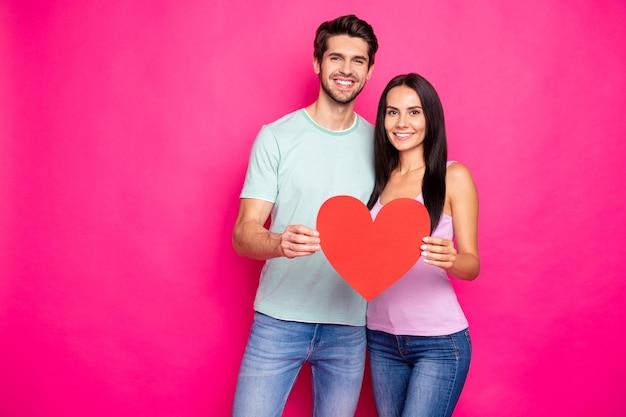 Foto van geweldige kerel en dame knuffelen met groot papieren hart in handen die positieve houding uitdrukken dragen casual outfit geïsoleerde roze kleur achtergrond Premium Foto