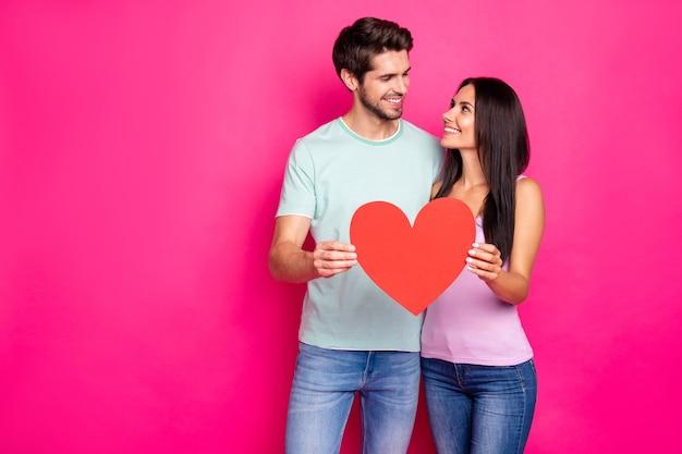 Foto van geweldige man en dame knuffelen met groot papieren hart in handen die beste gevoelens uitdrukken dragen casual outfit geïsoleerde roze kleur achtergrond Premium Foto