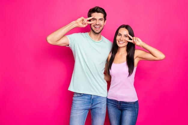 Foto van grappige paar man en dame verhogen handen tonen v-teken symbolen in de buurt van ogen dragen vrijetijdskleding geïsoleerde fel roze kleur achtergrond Premium Foto
