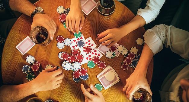 Foto van het bovenaanzicht van vrienden zitten aan houten tafel. vrienden plezier tijdens het spelen van bordspel. Gratis Foto