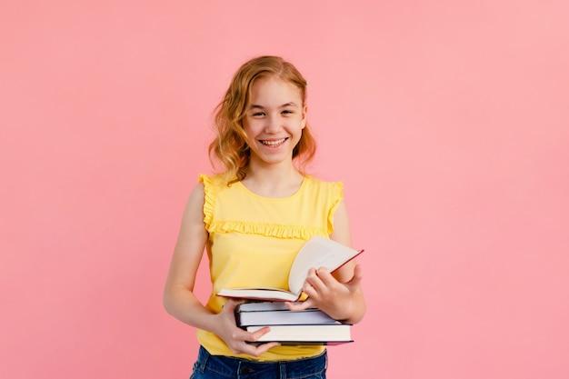Foto van het gelukkige charmante blonde meisje stellen met schriften en glimlachen geïsoleerd op roze achtergrond Premium Foto