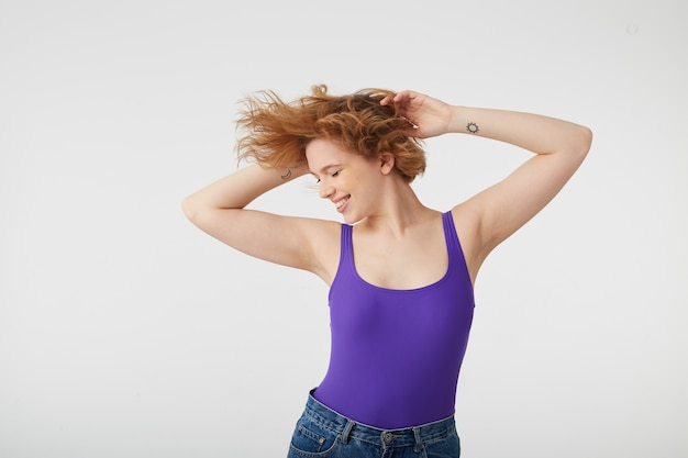 Foto van jonge gelukkig schattig korthaar meisje draagt in paars shirt dansen met opgeheven armen, haren vliegen uit elkaar in verschillende richtingen, genieten van muziek en leven. Gratis Foto