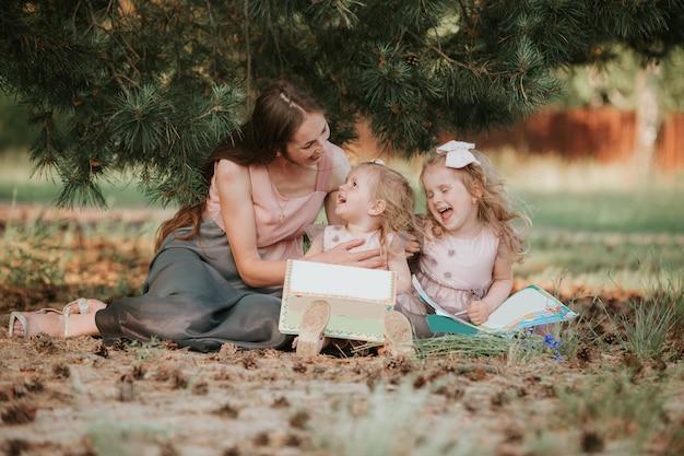 Foto van jonge moeder met twee schattige kinderen lezen boek buiten in het voorjaar, gelukkige moeder die haar kinderen in het park onderwijst, gelukkige familie, moeder en twee dochters. moederdag concept Premium Foto