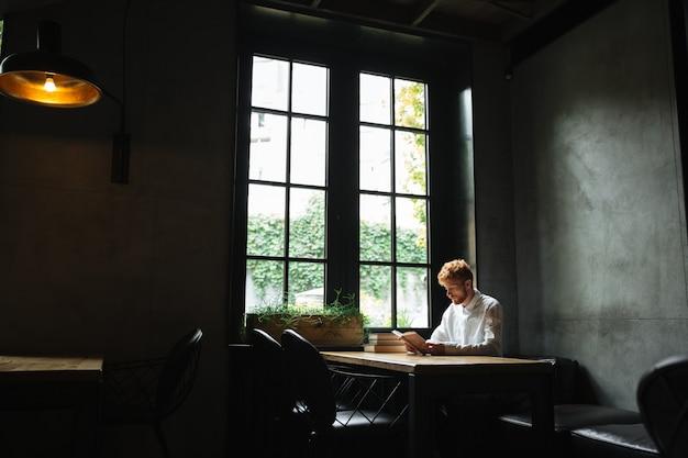 Foto van jonge roodharige bebaarde man in wit overhemd het lezen van een boek in de cafetaria Gratis Foto