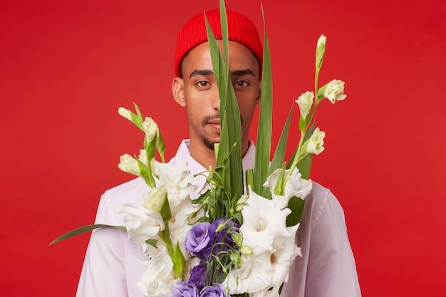 Foto van jonge rustige donkere man, draagt in wit overhemd en rode hoed, kijkt naar de camera via boeket, staat op rode achtergrond. Gratis Foto