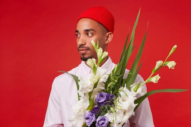 Foto van jonge rustige donkere man, draagt in wit overhemd en rode hoed, kijkt weg en houdt boeket vast, staat op rode achtergrond. Gratis Foto