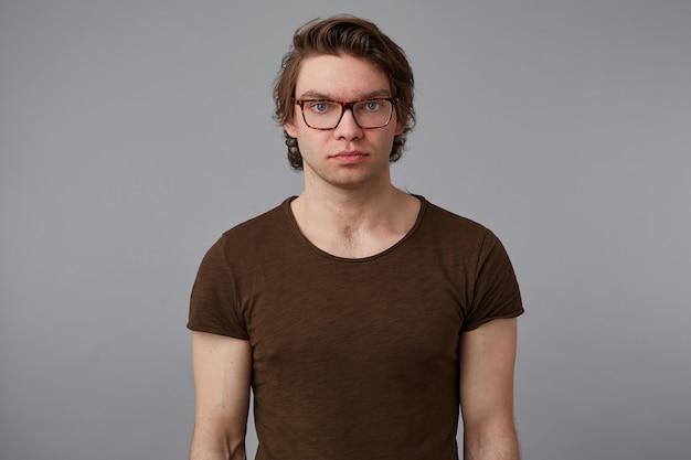 Foto van jonge serieuze man met bril draagt in een leeg t-shirt, staat over grijze achtergrond en kijkt naar de camera zonder emoties. Gratis Foto