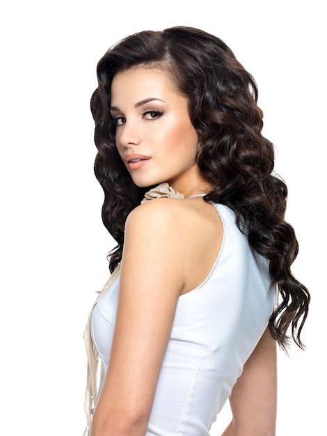 Foto van jonge vrouw met schoonheids lang krullend haar. mannequin - zijaanzichtportret. Gratis Foto