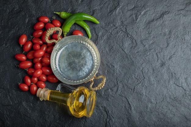 Foto van kersentomaat, groene paprikakoekenpan en fles olie. hoge kwaliteit foto Gratis Foto