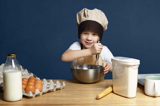 Foto van kleine jongen die schort en chef-kok glb draagt ?? ingrediënten in een metalen kom zwaait tijdens het koken van pannenkoeken, koekjes of ander gebak, staande aan de keukentafel met eieren, melk, bloem en deegroller Gratis Foto