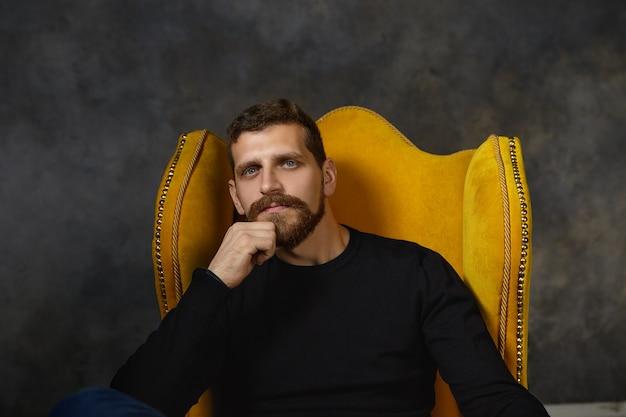 Foto van knappe jonge blanke bebaarde man met elegante zwarte trui ontspannen in luxe gele fauteuil, hand in zijn kin, peinzend, met nadenkend doordachte uitdrukking Gratis Foto
