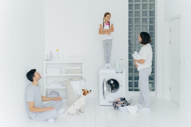 Foto van man en vrouw, hun hond en dochter doen huishoudelijk werk in wasruimte Premium Foto