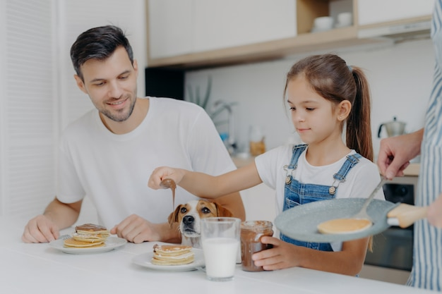 Foto van meisje in denim tuinbroek voegt chocolade toe aan pannenkoeken, ontbijt samen met vader en hond, houdt van hoe moeder kookt. familie in de keuken ontbijten tijdens het weekend. gelukkig moment Premium Foto