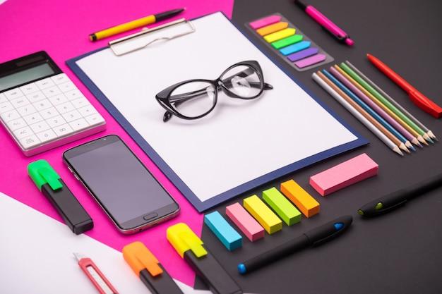 Foto van moderne artspace met klembord, glazen, briefpapier en smartphone op roze en zwart. Premium Foto
