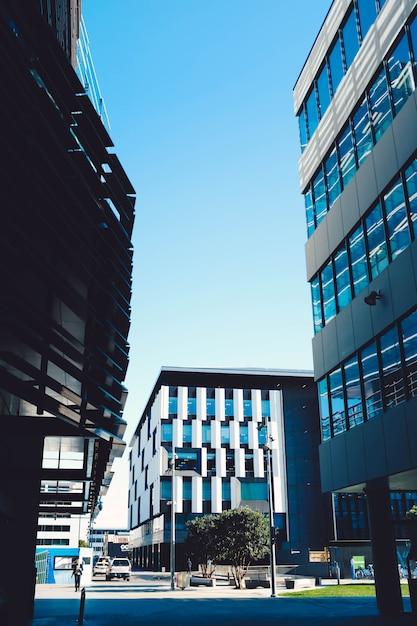 Foto van moderne wolkenkrabbers met blauwe ramen en een parkeerplaats onder een blauwe hemel Gratis Foto