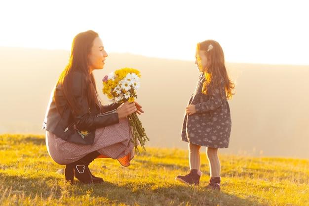 Foto van moeder bloemen geven voor haar dochtertje tijdens zonsondergang Premium Foto