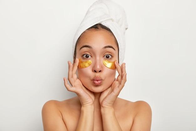 Foto van mooi vrouwelijk model past gele kussentjes toe onder de ogen om rimpels te verminderen, heeft anti-verouderingsprocedures, houdt de lippen gevouwen, staat shirtless binnenshuis, gewikkelde handdoek op het hoofd. cosmetologie concept Gratis Foto