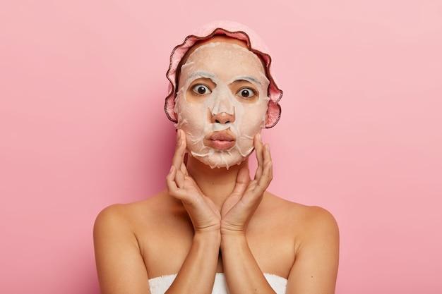 Foto van mooie aziatische vrouw heeft een voedend vochtinbrengende papieren masker op het gezicht, raakt de wangen zachtjes aan, houdt de lippen gevouwen, draagt een roze douchemuts, staat alleen. huidverzorging en schoonheidsbehandelingen concept Gratis Foto