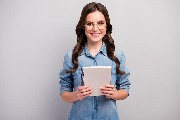 Foto van mooie freelancer dame houd papier planner ijverige betrouwbare student toothy glimlachen slijtage specs casual jeans denim overhemd geïsoleerde grijze kleur Premium Foto