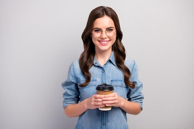 Foto van mooie freelancer dame houden papieren beker warme koffie drank hebben pauze werkproces slijtage specificaties casual jeans denim overhemd geïsoleerde grijze kleur Premium Foto
