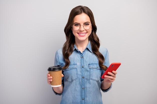Foto van mooie freelancer dame houden papieren beker warme koffie drank hebben werk pauze browsen telefoon apparaat slijtage specificaties casual jeans denim overhemd geïsoleerde grijze kleur Premium Foto