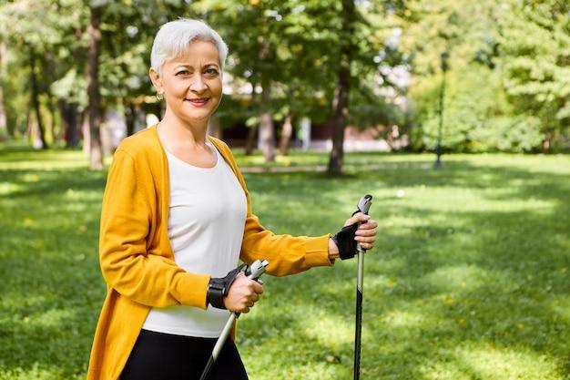 Foto van mooie vrolijke oudere volwassen vrouw in geel vest met stokken voor nordic walk, genietend van een actieve gezonde levensstijl, vol energie, met een gelukkige glimlach Gratis Foto