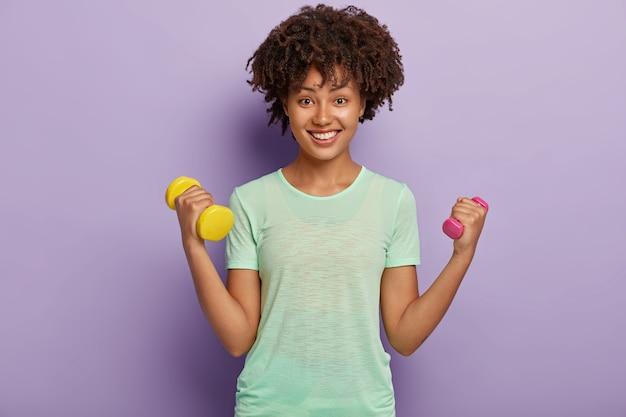 Foto van mooie vrolijke sterke vrouw heft twee armen met halters, traint biceps, draagt casual t-shirt, wil gezond en fit zijn, ziet er gelukkig uit met brede glimlach. sport, kracht van vrouwen Gratis Foto