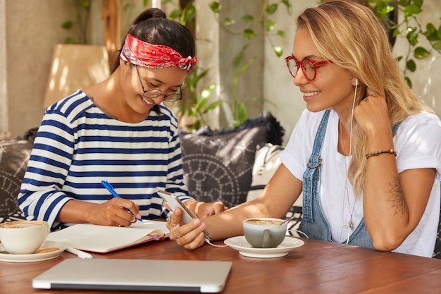 Foto van multi-etnische collega's bespreken ideeën voor een nieuw zakelijk project, hebben vrolijke uitdrukkingen in cafetaria met koffie. blonde vrouw luister audiotrack in oortelefoons, aziatisch meisje schrijft in dagboek Gratis Foto