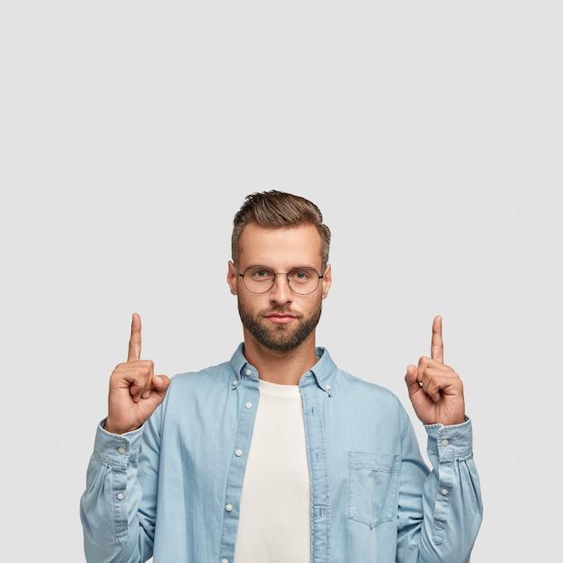 Foto van ongeschoren hipster gekleed in casual shirt, wijst met beide wijsvingers naar boven. Gratis Foto
