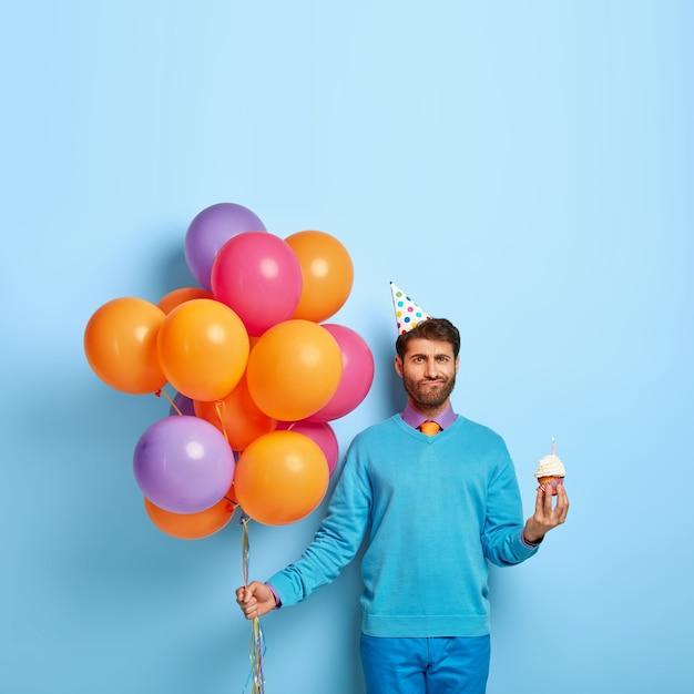 Foto van ongeschoren man met verjaardagshoed en ballonnen poseren in blauwe trui Gratis Foto