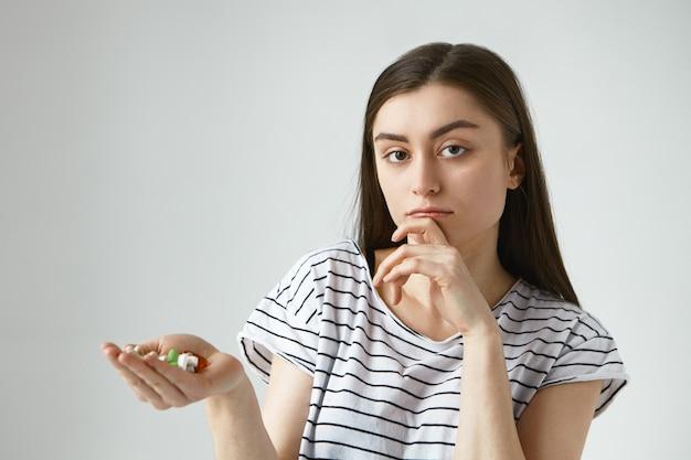 Foto van onzekere jonge brunette vrouw die een mondvol kleurrijke pillen vasthoudt, een bedachtzame twijfelachtige uitdrukking heeft, de kin aanraakt, eraan denkt medicatie te nemen of niet terwijl ze aan verkoudheid lijdt Gratis Foto