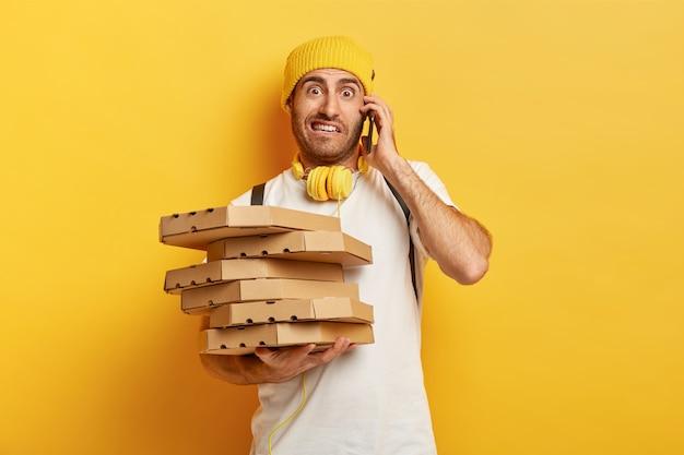 Foto van pizzaman ontvangt bestellingen van klanten via smartphone, houdt veel kartonnen dozen met fastfood vast, heeft een onaangename blik om met ontevreden klant te praten. service en leveringsconcept Gratis Foto
