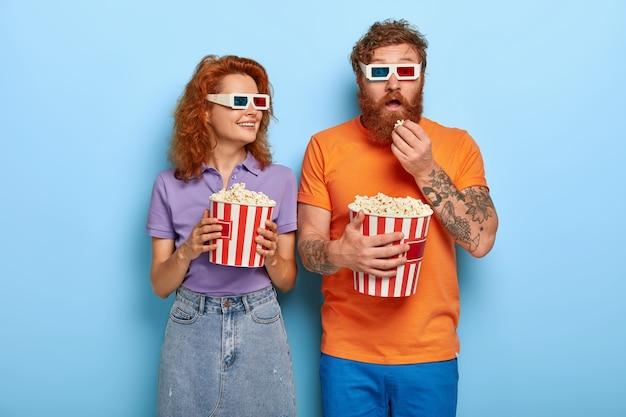 Foto van roodharige vrouwelijke en mannelijke paar kijken naar film in bioscoop theater Gratis Foto