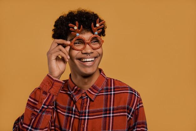 Foto van schattige afrikaanse mannelijke boer draagt kerstbril en glimlacht. man draagt geruite overhemd, geïsoleerde bruine kleur achtergrond. Premium Foto