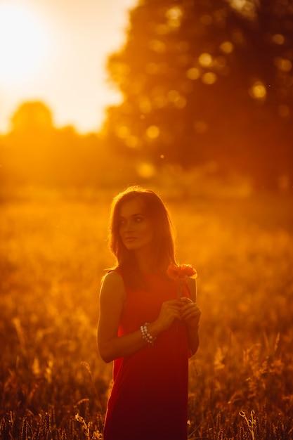Foto van schitterende dame in rode kleding die zich op gouden de zomergebied bevindt Gratis Foto