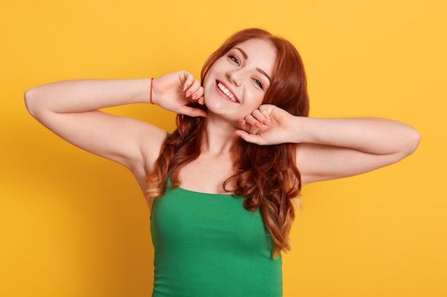 Foto van sterk roodharige vrouw met groene casual t-shirt, geeft aan op gele muur, glimlachend rechtstreeks in de camera kijken Premium Foto