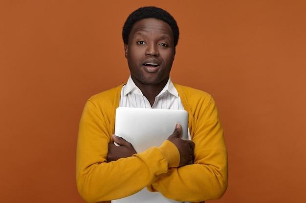 Foto van stijlvolle jonge donkere manager in geel vest met generieke laptop, kantoor verlaten na het werk. mensen, moderne technologie, baan, beroep en elektronische gadgetsconcept Gratis Foto