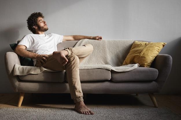 Foto van stijlvolle knappe jonge kerel met pluizige baard, volumineus kapsel en blote voeten met gesloten ogen, in slaap vallen of luisteren naar klassieke muziek, genieten van vrije tijd, zittend op de bank Gratis Foto