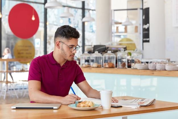 Foto van stijlvolle man met trendy kapsel, records schrijft in kladblok, gericht in de krant, afhaalmaaltijden koffie drinkt, moderne laptopcomputer gebruikt voor freelance werk. hipster-man maakt opnames Gratis Foto