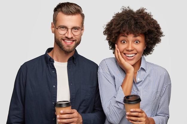 Foto van tevreden gemengd ras vrouw en man houdt wegwerp kopje koffie Gratis Foto