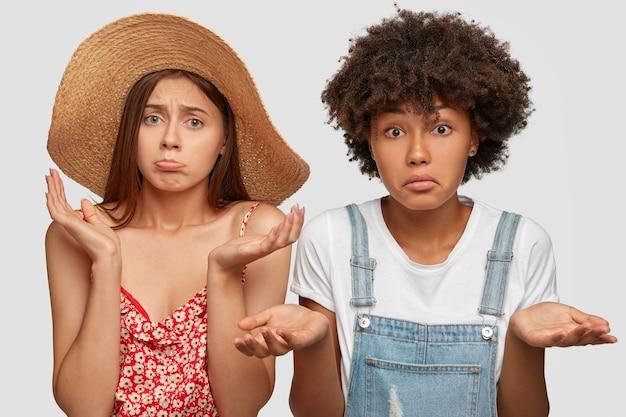 Foto van verbaasde aarzelende vrouwen van gemengd ras kijken met clueless uitdrukkingen Gratis Foto