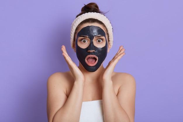 Foto van verbaasde sprakeloze vrouw met geopende mond, draagt een modder gezichtsmasker, heeft schoonheidsprocedures, meisje met geschokte uitdrukking, handdoek op lichaam gewikkeld, geïsoleerd op lila muur, houdt handpalmen dichtbij gezicht. Gratis Foto