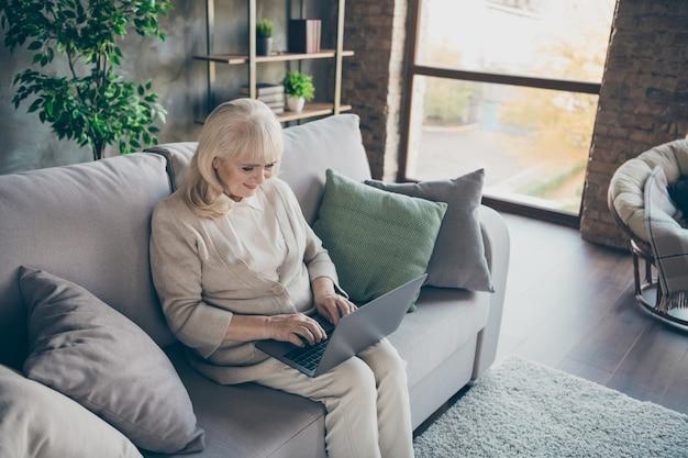 Foto van verbazingwekkende blonde leeftijd oma laptop lezen kleinkinderen e-mail typen antwoord zitcomfort sofa divan woonkamer binnenshuis Premium Foto
