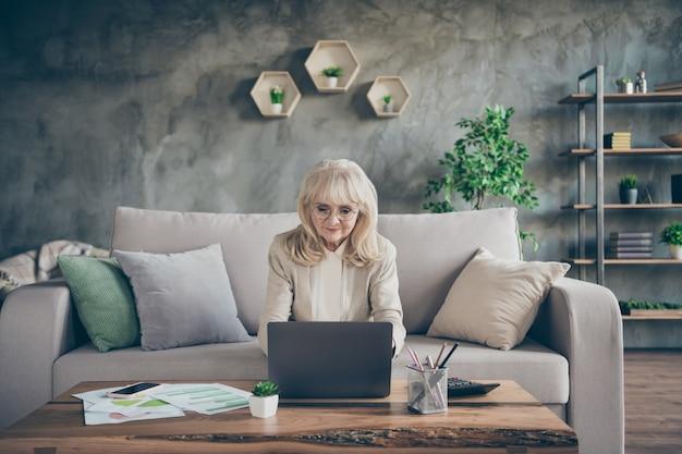 Foto van verbazingwekkende witte haren leeftijd oma laptop lezen e-mail typen antwoord collega's partners zitten comfort sofa divan woonkamer office stijl binnenshuis Premium Foto
